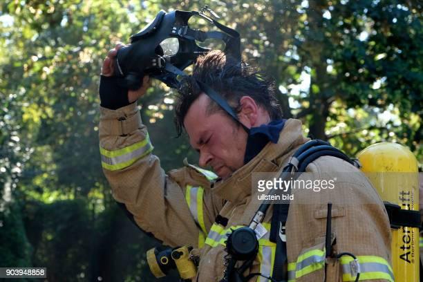 Feuerwehrmann nimmt nach dem Löscheinsatz seine Atemschutzmaske ab - Berliner Feuerwehr bei Löscharbeiten bei einem Wohnungsbrand in der Soldiner...
