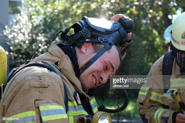 Feuerwehrmann nimmt nach dem Löscheinsatz seine Atemschutzmaske ab Berliner Feuerwehr bei Löscharbeiten bei einem Wohnungsbrand in der Soldiner...