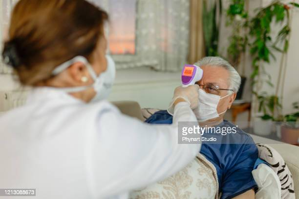 fever of the patient under observation at home is measured - infectious disease stock pictures, royalty-free photos & images