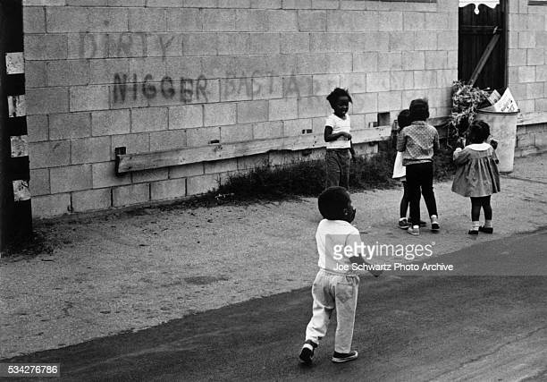 A few African Americans play on a sidewalk near some very racist grafitti in Santa Monica California 1970s