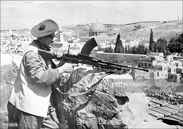 A few days before the British Mandate over Palestine ended a British soldier holding a Britishmade Bren machine gun stands guard at the demarcation...