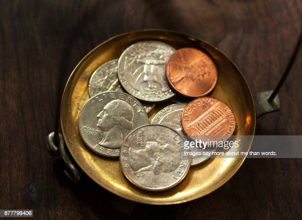 A few dollar coins on plate in an old scale of weighing gold.