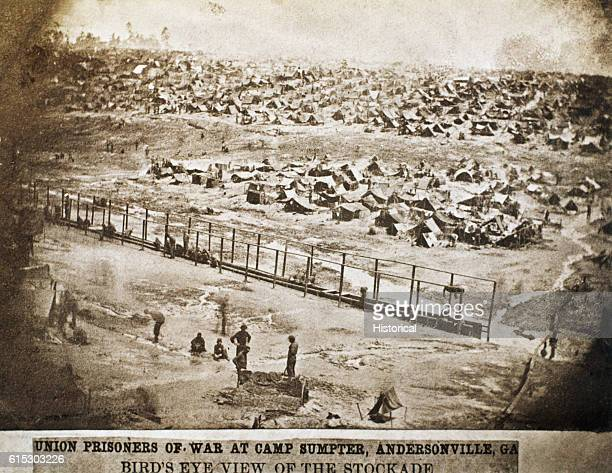 A few federal prisoners of war squat along a long slit trench used as a latrine at Andersonville Georgia Originally known as Camp Sumter the...