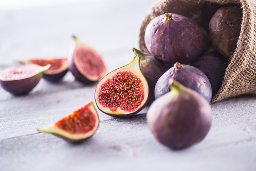 A few figs freely lying on old wooden table. 1048680440