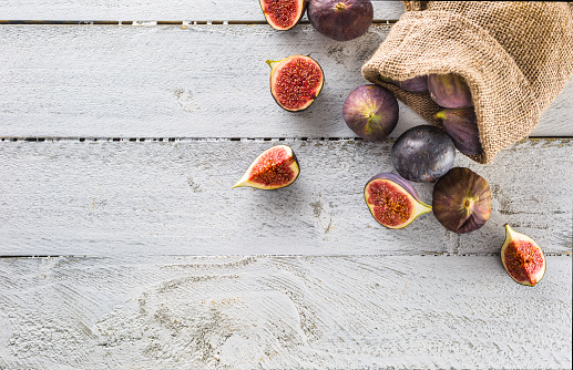 A few figs freely lying on old wooden table. 1048680466