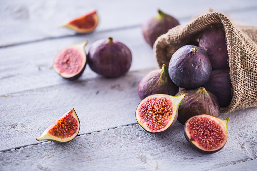 A few figs freely lying on old wooden table. 1048680480