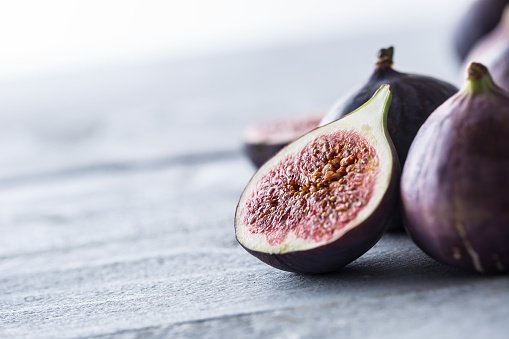 A few figs freely lying on old wooden table. 1048680958