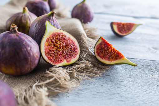 A few figs freely lying on old wooden table. 1048680972