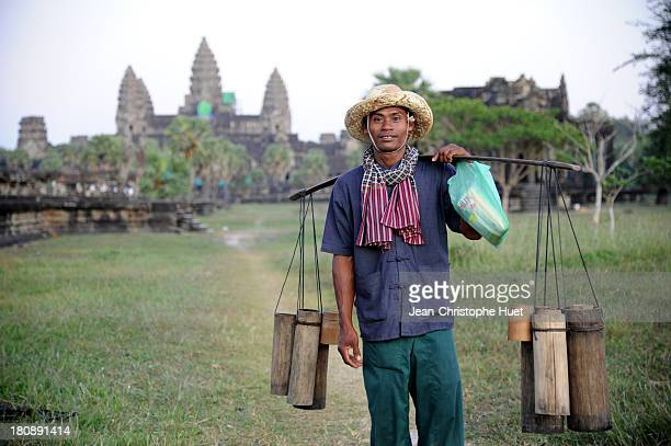 CONTENT] A few meters only from the tourist crowd in front of the famous Angkor Wat temple a palm wine seller
