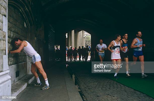 A few miles from the finish line this longdistance runner has stopped in agony to lean against the walls beneath Tower Bridge during th London...