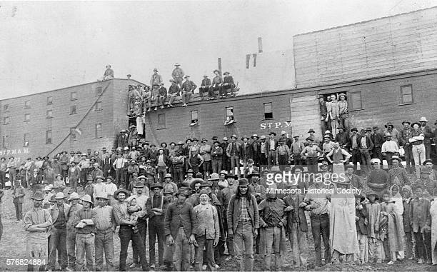 A few Native Americans mingle with a crowd of track layers standing by large dormintory cars in which they slept during the laying of track between...