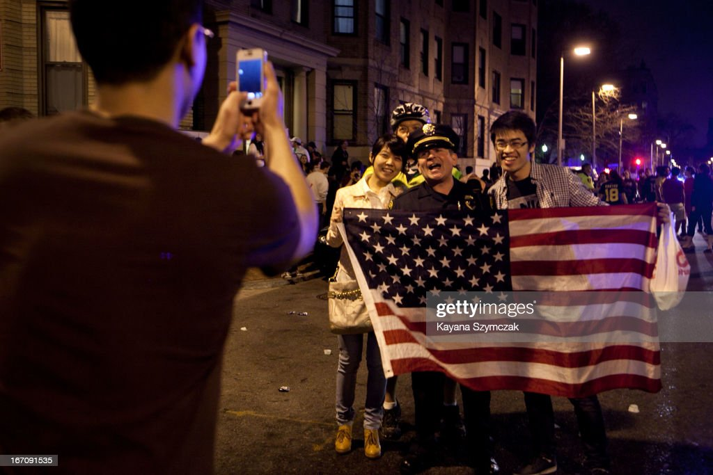 A few of the estimated 200 people who poured onto Hemingway Street in the Fenway neighborhood to celebrate after the announcement earlier of the capture of the second Boston Martathon bombing suspect celebrate April 19, 2013 in Boston, Massachusetts. A manhunt for Dzhokhar A. Tsarnaev, 19, ended this evening with his capture on a boat parked on a residential property in Watertown, Massachusetts. His brother Tamerlan Tsarnaev, 26, the other suspect, was shot and killed by police early this morning after a car chase and shootout with police. The bombing killed three people and wounded at least 170.