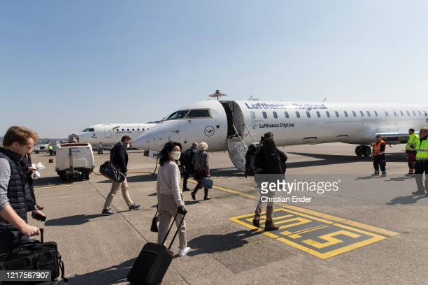 Few passengers wearing a protective face mask get on the plane at nearlyempty Zurich Airport during the coronavirus crisis on April 2 2020 in Zurich...