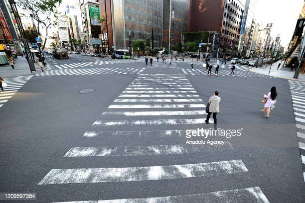 Few people are seen in a nearly empty street after the state of emergency declared to prevent the spread of coronavirus in Tokyo, Japan on April 10,...