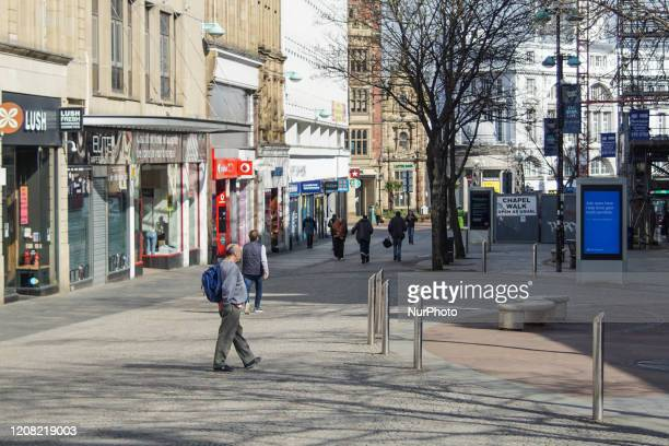 Few people can be seen to walk through the streets of Sheffield, England on 24 March 2020.