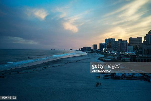 A few people stroll along a beach in Atlantic City New Jersey on May 8 2016 Atlantic City the famous US gambling resort town and setting for hit TV...