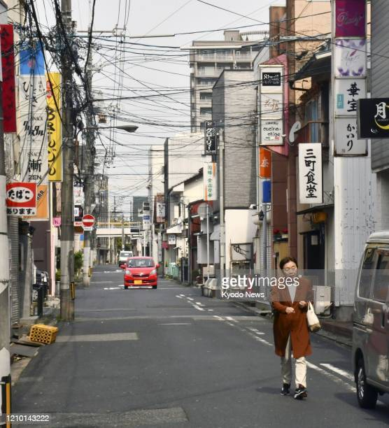 Few people walk in a downtown area in Tottori, western Japan, on April 17 after a state of emergency was expanded from some urban areas to the entire...