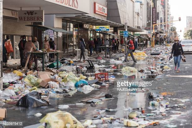 Few people walk in Dr. Pixley Ka Seme street strewn with dirt and filth caused after five days of looting in Durban on July 14, 2021 as several...