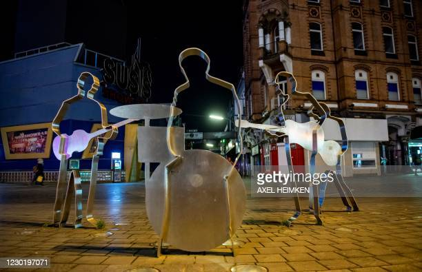 Few people walk past the Beatles-Platz Square with five life-sized silhouettes of the band members of the famous The Beatles near the Grosse Freiheit...