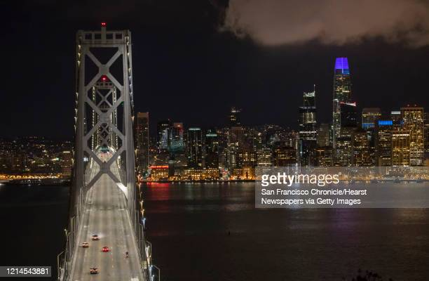 A few vehicles make their way across the Bay Bridge after midnight as the city shut down following an order to shelter in place in San Francisco...