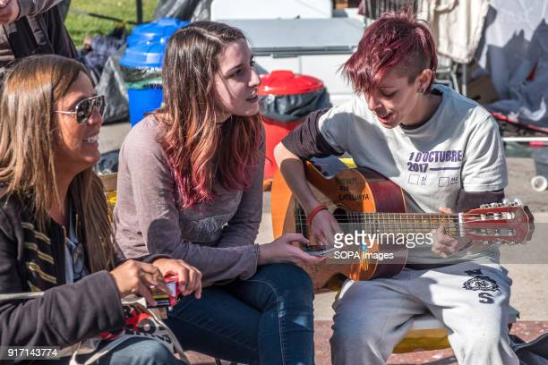 A few young girls spend their time singing and playing the guitar Several tents occupy the Plaza Catalunya in Barcelona to claim Carles Puigdemont as...
