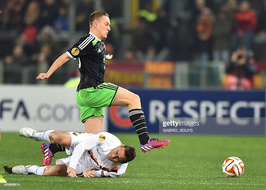 Feyenoord's midfielder Jens Toornstra (top) vies with Roma's forward Francesco Totti during the UEFA Europa League round of 32 match AS Roma vs Feyenoord at the Olympic Stadium in Rome on February 19, 2015.