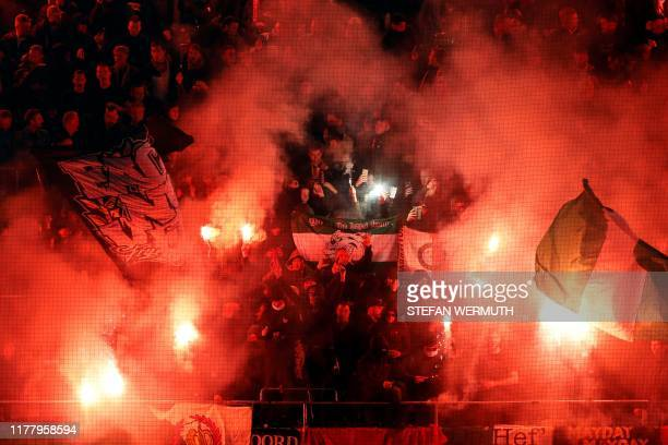 Feyenoord's supporters burn flares and wave flags during the Europa League Group G football match between BSC Young Boys and Feyenoord at the Stade...
