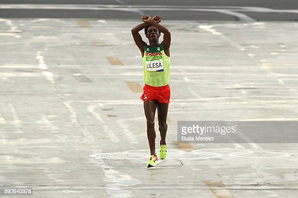 Feyisa Lilesa of Ethiopia celebrates as he crosses the line to win silver during the Men's Marathon on Day 16 of the Rio 2016 Olympic Games at...