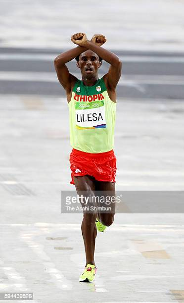 Feyisa Lilesa of Ethiopia crosses the line to win silver medal in the Men's Marathon on Day 16 of the Rio 2016 Olympic Games at Sambodromo on August...