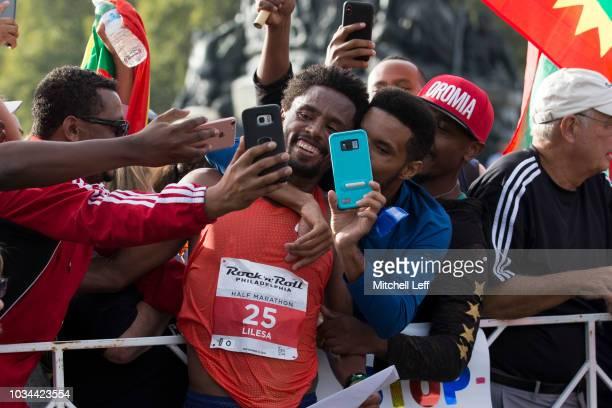 Feyisa Lilesa takes selfies after the Rock 'n' Roll Philadelphia Half Marathon on September 16 2018 in Philadelphia Pennsylvania
