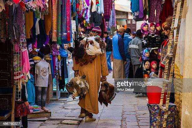 Fez medina colorful street and man carrying chiken