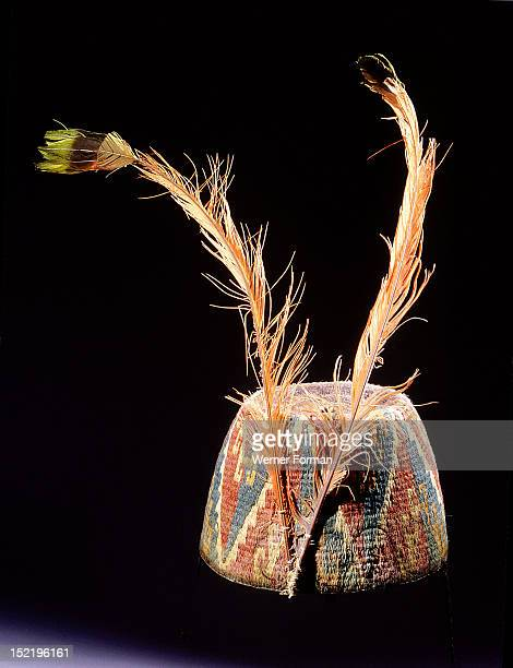 Fez style hat of coloured and twisted llama threads looped into coils, with triangular and step volute design, It is decorated with two orange...
