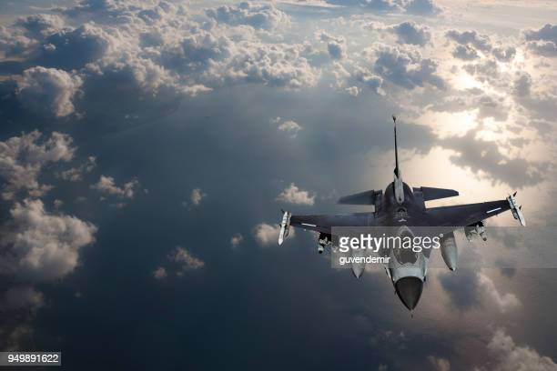 fıghter jet in fligh over the sea at sunset - military airplane stock pictures, royalty-free photos & images
