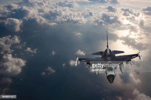 Fıghter Jet in fligh over the sea at sunset