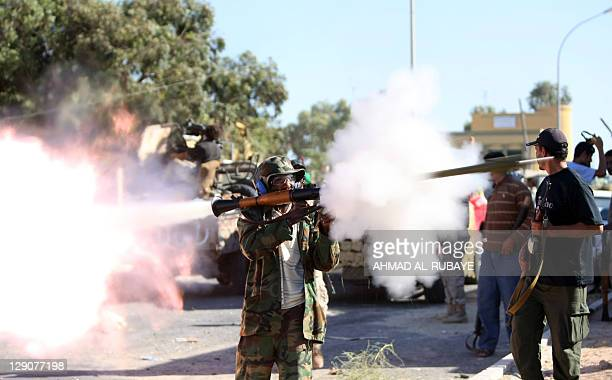A fghter loyal to Libya's new regime fires an RPG during fighting in the town of Sirte on October 12 as they move in for the kill against Moamer...