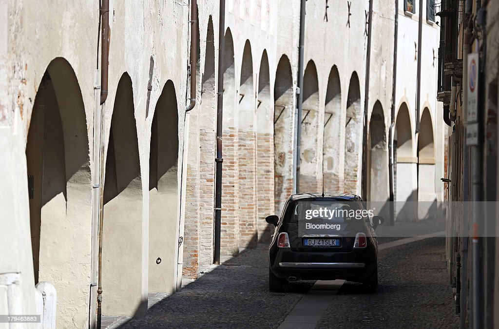 A Fiat 500 automobile, produced by Fiat SpA, drives past the archways of residential buildingsin Treviso, Italy, on Tuesday, Sept. 3, 2013. Italy's Agriculture Ministry has begun to investigate suspected sales of imitation Prosecco sparkling wine in its native Veneto region. Photographer: Alessia Pierdomenico/Bloomberg via Getty Images