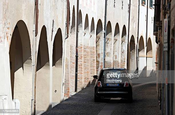 A Fiat 500 automobile produced by Fiat SpA drives past the archways of residential buildings in Treviso Italy on Tuesday Sept 3 2013 Italy's...