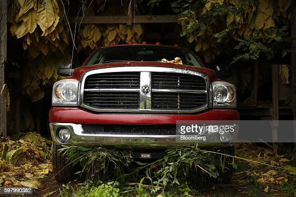 A Fiat Chrysler Automobiles NV Dodge Ram pickup truck sits parked inside a barn as burley tobacco leaves grown by Tucker Farms hang in Shelbyville...