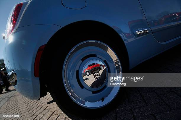 A Fiat SpA Strada Double Cab vehicle is reflected in the wheel of a 1957 Fiat 500 standing in front of the Chrysler Group LLC headquarters in Auburn...