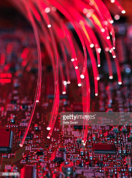 Fibre optics flowing through circuit boards from a laptop computer, close-up