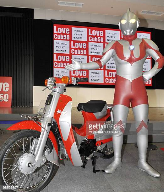 """Fictional action character Ultraman displays a """"Super Cub"""" motorcycle at the Honda headquarters in Tokyo on February 12, 2010. Some 60 specially..."""