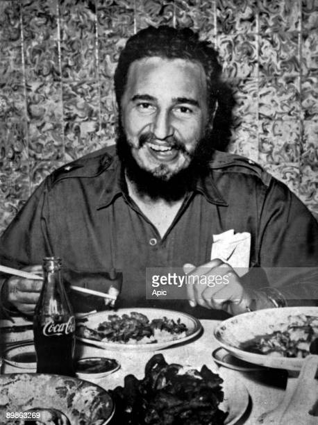 Fidel castro head of cuban state eating a chinese meal with chopsticks and drinking Coca Cola c 1960