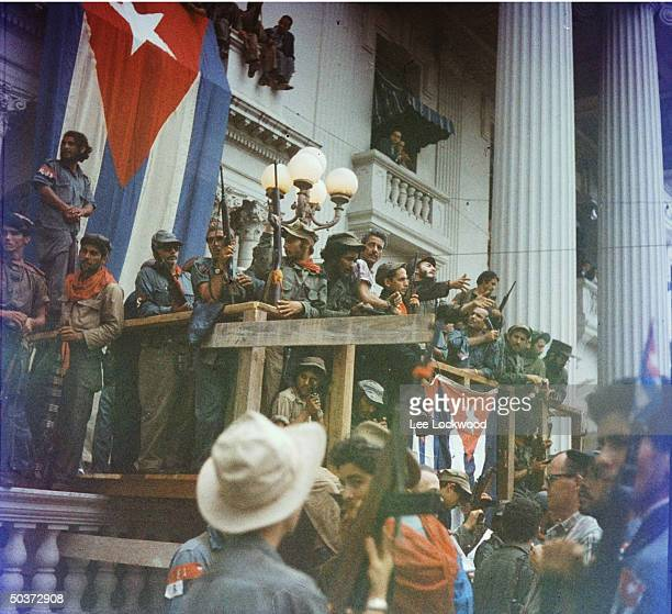Fidel Castro in Santa Clara orating from makeshift balcony draped w Cuban flags in Santa Clara en route to victorious entry into Havana