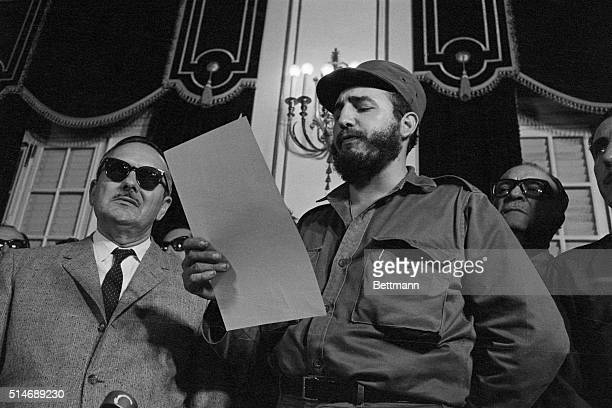 Fidel Castro reads the oath of office and is sworn in as prime minister of Cuba on February 16, 1959. At left is acting president Manuel Urrutia and...
