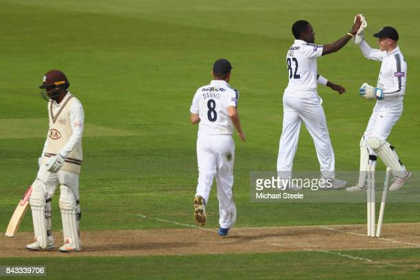 Fidel Edwards of Hampshire celebrates with wicketkeeper Tom Alsop after taking the wicket of Ryan Patel of Surrey during day two of the Specsavers...