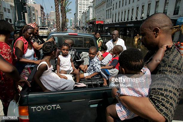 Fidelis Okonkwo holds his 7-month-old daughter Obina as he and his family load into a pickup truck on Canal Street August 31, 2005 in New Orleans,...