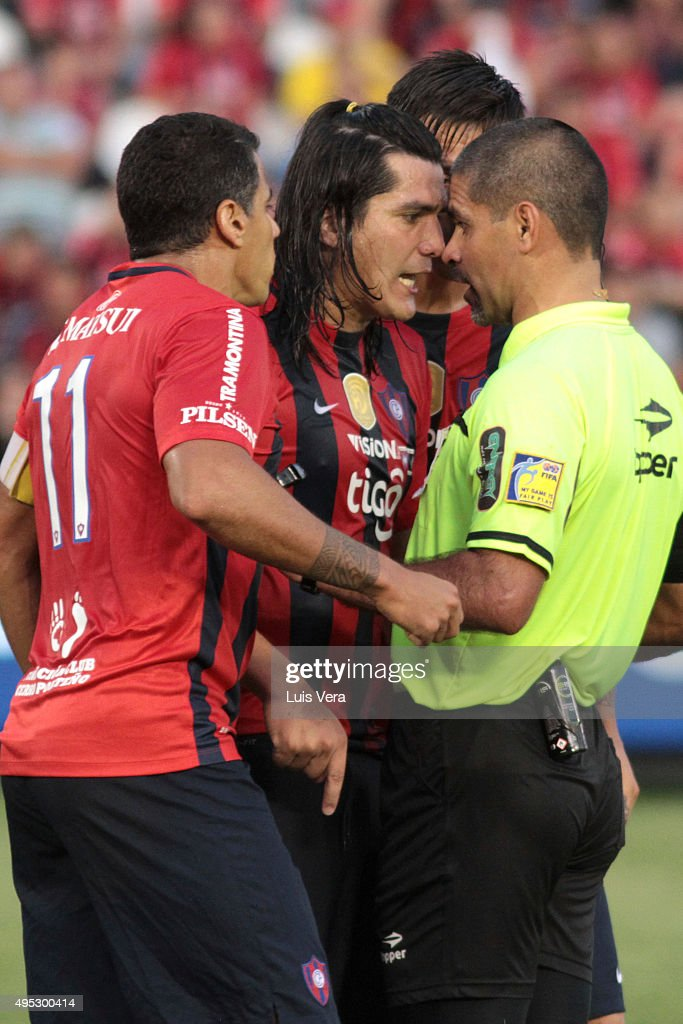 Fidencio Oviedo and Carlos Bonet of Cerro Porteño claims to the referee Eber Aquino, during a match between Cerro Porteño and Olimpia as part of 17th round of APF Torneo Apertura 2015 at Defensores del Chaco Stadium on November 01, 2015 in Asuncion, Paraguay.