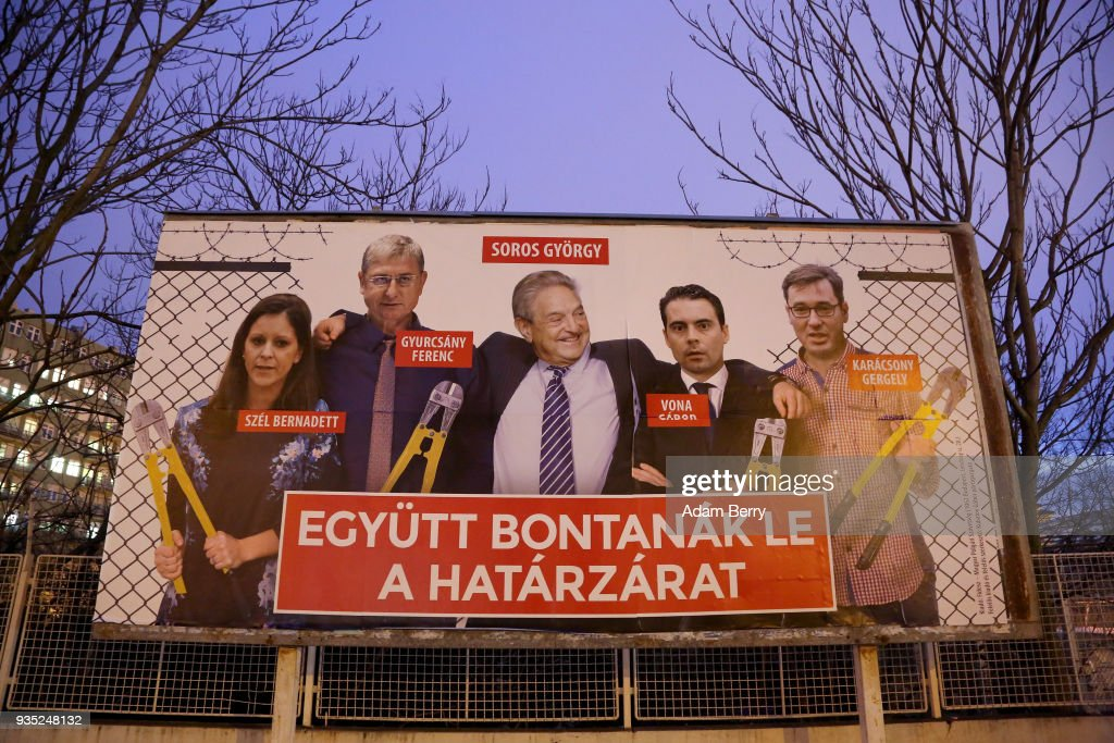 A Fidesz-party sponsored poster featuring a montage of billionaire investor George Soros (C) posing with (L to R) Politics Can Be Different (Lehet Mas a Politika, or LMP) party candidate Bernadett Szel, former Hungarian prime minister and Democratic Coalition (Hungarian: Demokratikus Koalicio, or DK) party candidate Ferenc Gyurcsany, Jobbik party candidate Gabor Vona, and Dialogue for Hungary (Parbeszed Magyarorszagert) party candidate Gergely Karacsony, all holding bolt cutters after having cut the border fence behind them, hangs prior to the upcoming Hungarian parliamentary elections on April 8, on March 20, 2018 in Budapest, Hungary. Incumbent Prime Minister Viktor Orban faces only a few disorganized opposition parties standing in the way of a possible third term, although the popularity of his own, Fidesz, once a liberal student movement and now advocating an increasingly anti-immigrant, anti-European Union platform after dominating Hungarian politics on both national and local levels since 2010, has fallen since December. It suffered a surprising setback last month in its southern town stronghold of Hodmezovasarhely, when an opposition-backed independent won an easy victory, giving hope to other contenders for success in the national elections in early April.