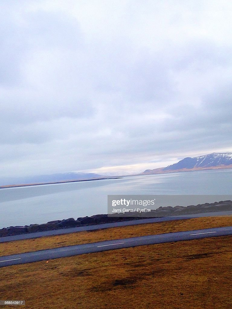 Field And Road By River Against Cloudy Sky : Stock Photo
