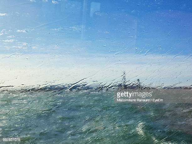field and sky seen through wet glass window - massimiliano ranauro stock pictures, royalty-free photos & images